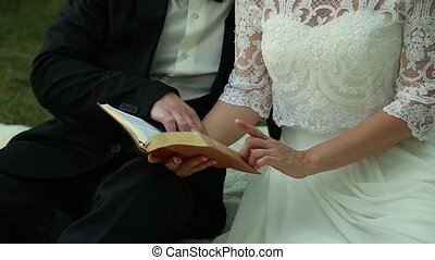 Yong bride and groom sitting in the park and ridding the book