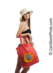 Yong girl walk with red beach bag and straw hat