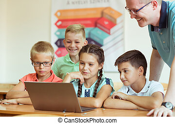 Yong handsome teacher with group of clewer children working with laptop at school