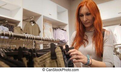 Yong positive woman is choosing a dress in women's clothing store