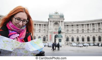 Yong tourist - woman with red hair and glasses looking map in Heldenplatz, Vienna