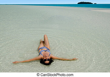 Yong woman bathing on Aitutaki Lagoon, Cook Islands.