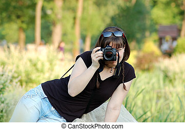 Yong woman photographer with camera in park