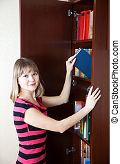 woman selecting book in bookcase