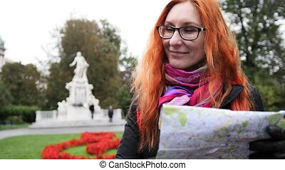 Yong woman tourist with red hair and glasses looking map in Burggarten, Vienna, Austria
