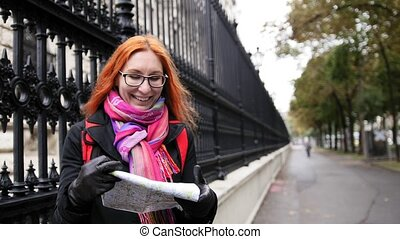 Yong woman tourist with red hair and glasses looking map in Vienna near Neue Burg, Austria