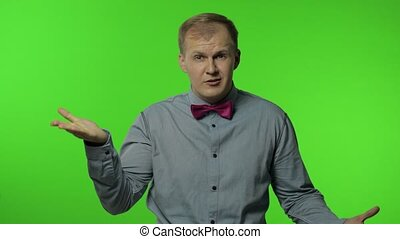 You are crazy, out of mind! Displeased annoyed man in gray shirt pointing at camera and showing stupid gesture, blaming some idiot for insane plan. Portrait of guy posing on chroma key background