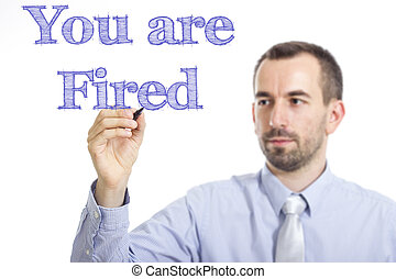 You are Fired - Young businessman writing blue text on transparent surface