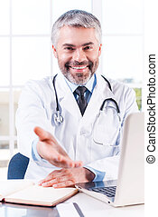 You can trust me! Confident mature grey hair doctor stretching out hand and smiling while sitting at his working place