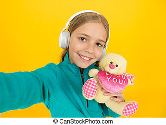 You create my heart smile. Small child hold valentines teddy bear with pink heart. Love you heart inscription. You are in my heart. Happy Valentines day celebration. Inspired holiday gift