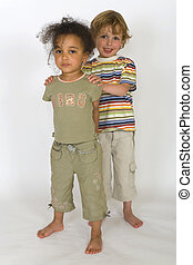 A beautiful mixed race girl with a blonde boy standing behind her pushing her forward