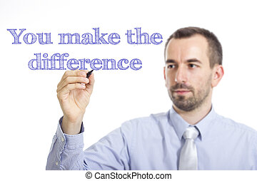 You make the difference - Young businessman writing blue text on transparent surface