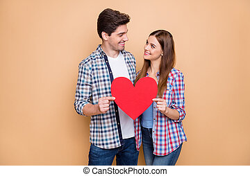 You my world. Portrait of romantic married spouses hold red big papercard heart look enjoy 14-february dream date wear checkered shirt isolated over beige color background