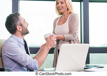 You need to have a break! Cheerful woman giving a cup of coffee to a man in formalwear sitting at his working place
