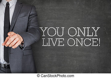 You only live once on blackboard with businessman finger...