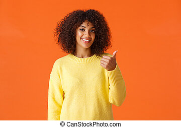 You should come and see it. Carefree good-looking hipster girl yellow sweater, inviting come inside pointing thumb behind herself and smiling, recommend product or company service, orange background