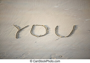 "You - The word \""you\\\"" is written by someone on sand"