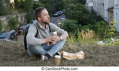 Youg man snacking outdoors