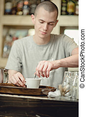 Youn waiter stirring espresso coffee for better froth
