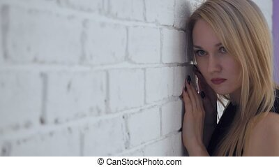 Yound beautiful sad woman posing near white brick wall.