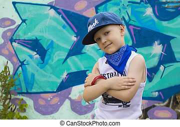 young 5-years boy posing in front of a colorful graffiti...