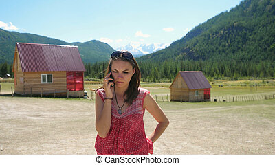 Young a little bit angry brunette woman talking with someone by smartphone while standing by the mountain in her moment of the travel