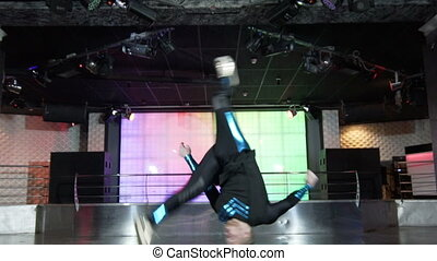 Young acrobat performing flips in club Slow motion