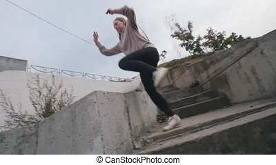 Young acrobatic girl in hoodie jumps over the barrier -...