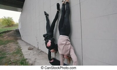 Young acrobatic girls standing on their hands near the wall....