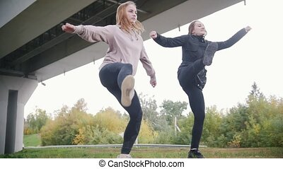 Young acrobatic girls synchronously performing split while...