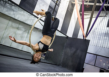 young acrobatic woman hanging on aerial hoop