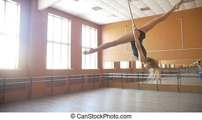 Young acrobatic woman shows flexibility on gymnastic hoop -...