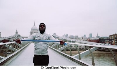 Young active black sportsman exercising with elastic rubber...