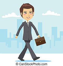 Young and handsome active businessman positively walking through the city's streets to attend a business meeting carrying a briefcase
