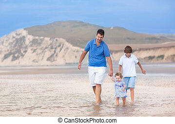 Young active father playing at a beautiful beach with his son an