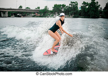 Young active girl riding on the wakesurf