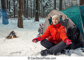 Young active tourist on a campaign sits near a tent in the winter forest