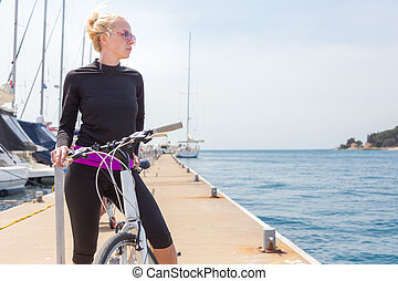 Young active woman cycling on pier in marina.