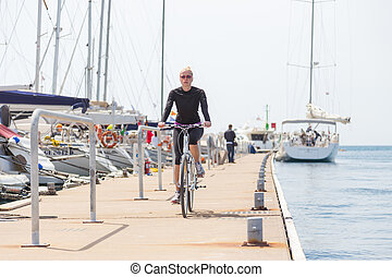 Young active woman cycling on pier in Rovinj marina, Istria, Croatia