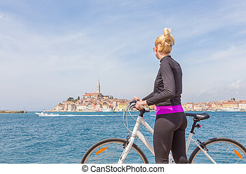 Young active woman cycling round Rovinj, Istria, Croatia. - ...