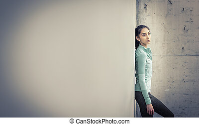 Young active woman leaning against wall