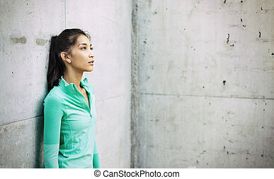 Young active woman leaning against