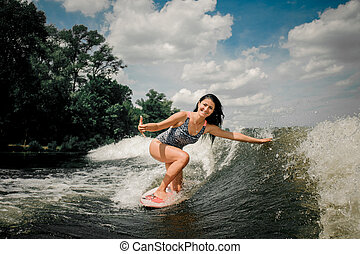 Young active woman riding on the wakeboard