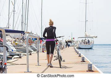Young active woman with cycling on pier in marina.
