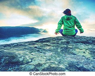 Young active woman with trekking equipment sitting, relaxing