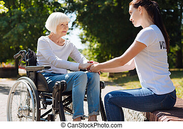 Young admirable woman being a psychotherapist for elderly lady