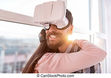 Young adorable couple hugging in VR glasses