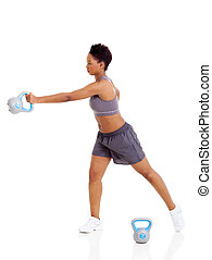 young adult afro american woman doing swing exercise with kettle bell on white background