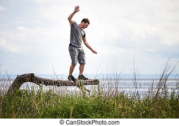 Young Adult Balancing on a Tree in Vacation