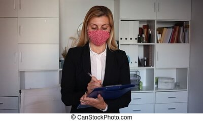 Young adult businesswoman in face mask standing with ...